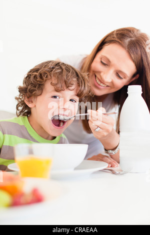 Mother feeding son cereal - Stock Photo