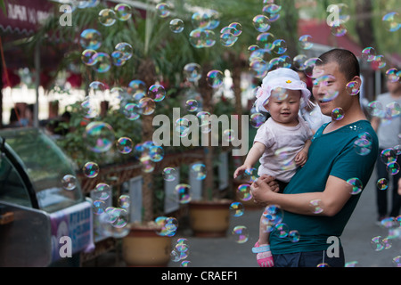 Chinese father and child, surrounded by bubbles, near QianHai Lake, in Beijing, China. - Stock Photo