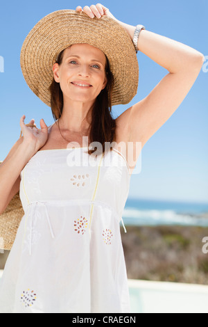 Woman wearing straw hat outdoors - Stock Photo