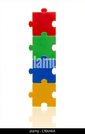 Four colourful puzzle pieces stuck on top of each other, connected, symbolic image for cohesion - Stock Photo