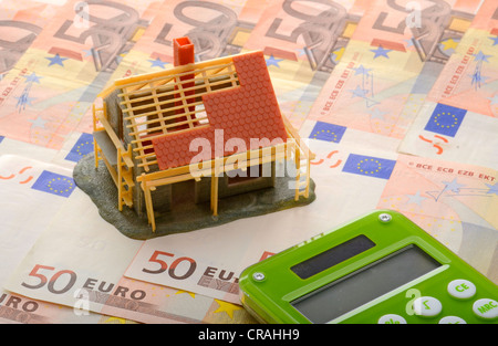 Miniature construction site with carport on 50 euro notes, symbolic image for building costs - Stock Photo