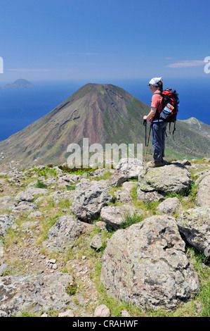 Hiker in front of a volcano on Salina, with the islands of Filicudi and Alicudi at the rear, Aeolian or Lipari Islands, - Stock Photo