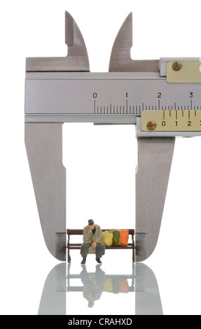 Homeless man in a caliper gauge, symbolic image for measuring poverty - Stock Photo