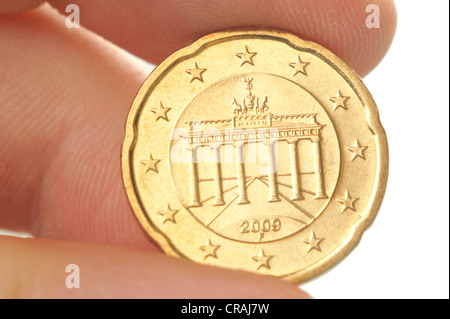 Fingers holding a twenty-cent euro coin with the Brandenburg Gate, macro - Stock Photo
