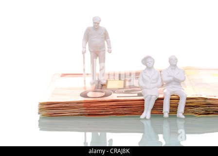 Pensioners, figures sitting on a stack of fifty euro banknotes, symbolic image for retirees putting their money - Stock Photo