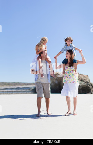 Parents carrying children on shoulders - Stock Photo