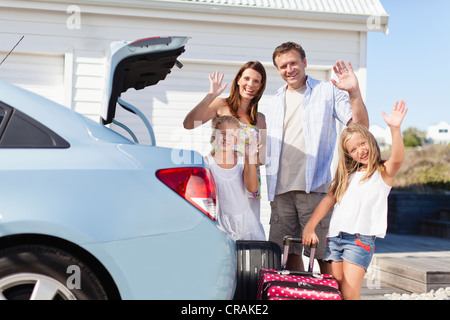 Family loading up car trunk for vacation - Stock Photo
