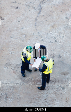 Workers reading blueprints at dry dock - Stock Photo