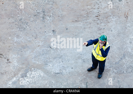 Worker using walkie-talkie on dry dock - Stock Photo