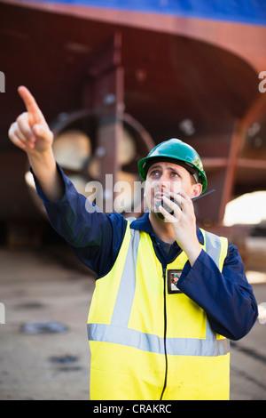 Worker using walkie talkie on dry dock - Stock Photo
