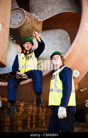 Workers talking in propeller on dry dock - Stock Photo
