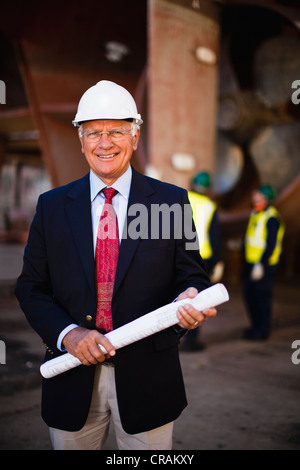 Businessman with blueprints on dry dock - Stock Photo