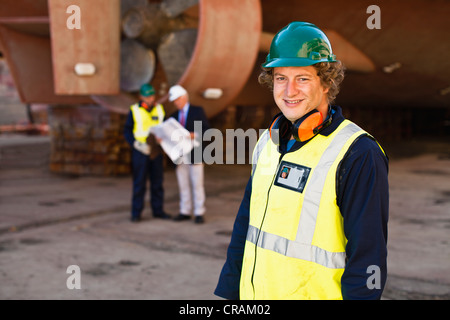 Smiling worker standing on dry dock - Stock Photo
