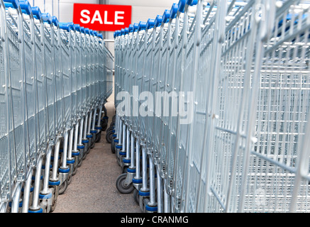 Supermarket shopping carts with SALE text label on a background - Stock Photo