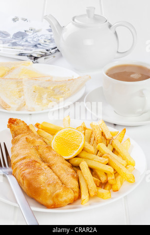 Fish and chips served with buttered bread and a pot of tea. Favourite British seaside supper. - Stock Photo