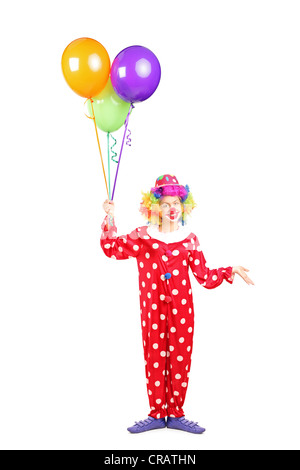 Full length portrait of a female clown, happy joyful expression on face, with a bunch of balloons isolated on white - Stock Photo
