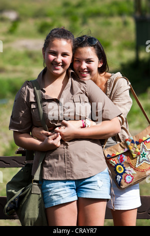 Two girls, about 13 and 18, wearing safari outfits leaning against on a railing, Masai Mara National Reserve, Kenya, - Stock Photo