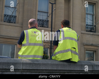The backs of two construction workers on a break sitting on a wall in London - Stock Photo