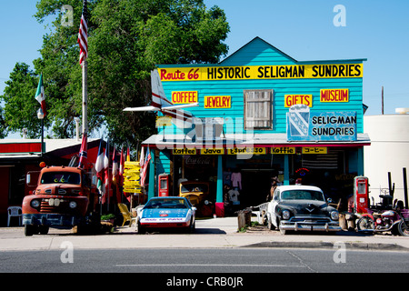 antique 60s automobiles stand in front of store along Main Street Route 66 in Seligman Arizona USA North America - Stock Photo