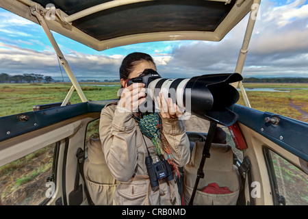 Young photographer taking pictures from a safari bus, Lake Nakuru National Park, Kenya, East Africa, PublicGround - Stock Photo
