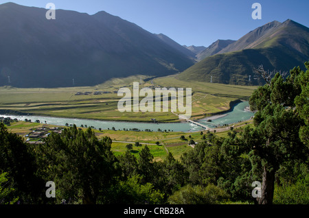 Reting river, Reting Tsangpo with centuries-old juniper trees in the mountains of Reting Monastery, Mount Gangi - Stock Photo