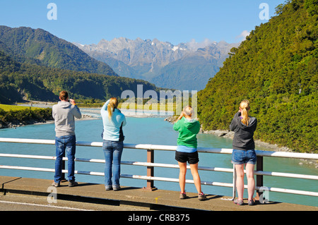 Tourists taking photographs of Whataroa River, looking towards the Southern Alps, West Coast of the South Island - Stock Photo