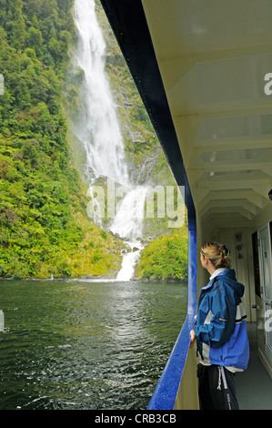 Woman leaning against the railing of the ship Fiordland Navigator, a waterfall at the back, Doubtful Sound cruise, - Stock Photo