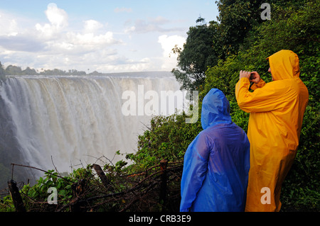 Tourists in rain jackets photographing the Victoria Falls, waterfall on the Zimbabwean side of the river Zambezi - Stock Photo