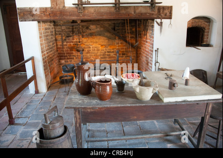 Pioneer style kitchen with brick oven and table with jars and pots - Stock Photo