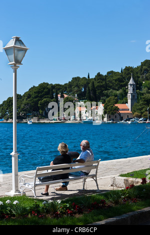 Retired couple sitting on a bench on the promenade of Cavtat, central Dalmatia, Dalmatia, Adriatic coast, Croatia, - Stock Photo
