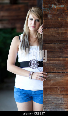 Young woman with long blonde hair standing next to a wooden wall - Stock Photo