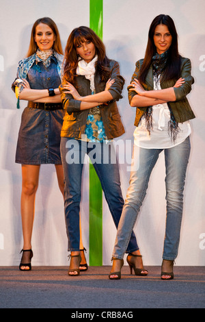Three models confidently standing on a stage - Stock Photo