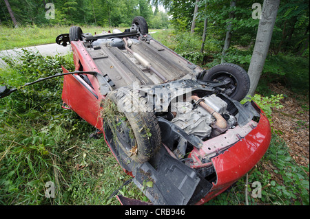 A damaged red Suzuki Swift is lying on its roof after a road traffic accident on the K 1209 road, Lichtenwald - Stock Photo