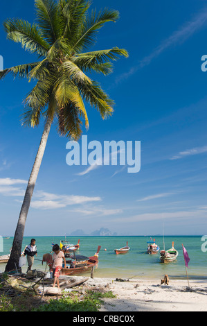 Children playing on the beach in the fishing village, Ko Muk or Ko Mook island, Thailand, Southeast Asia - Stock Photo