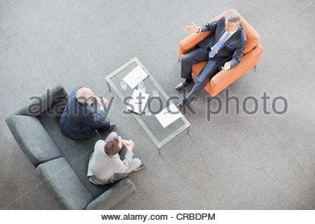 Businessmen meeting in lobby - Stock Photo