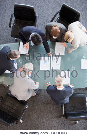 Business people huddled around paperwork on table - Stock Photo