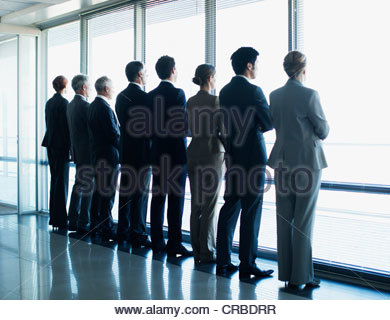Business people standing in a row and looking out window - Stock Photo