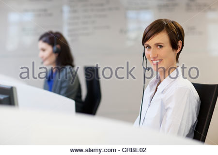 Portrait of smiling woman wearing headset - Stock Photo