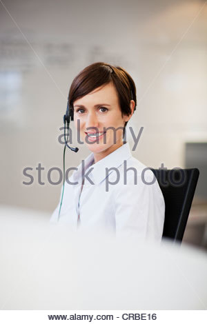 Portrait of smiling businesswoman wearing headset - Stock Photo