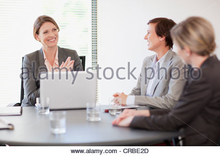 Smiling businesswomen with laptop meeting in conference room - Stock Photo