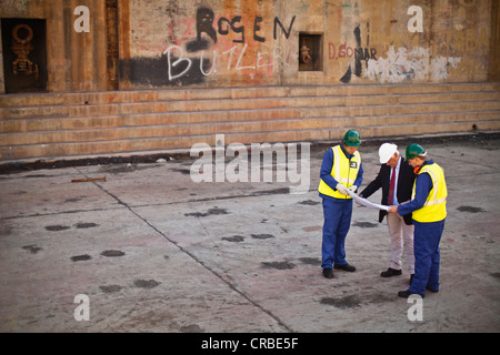 Workers reading blueprints on dry dock - Stock Photo