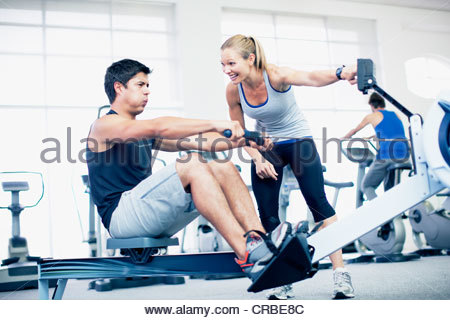 Personal trainer with man on rowing machine in gymnasium - Stock Photo
