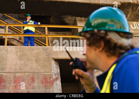 Workers using walkie talkies on dry dock - Stock Photo