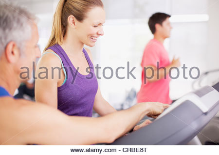 Man guiding woman on treadmill - Stock Photo