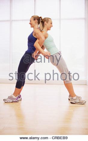 Women standing back to back in fitness studio - Stock Photo