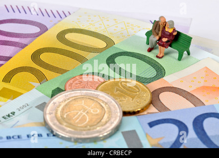 Miniature figurines of a retired couple sitting on a park bench on euro banknotes and coins, symbolic image for - Stock Photo