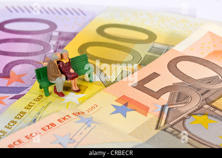 Miniature figurines of a retired couple sitting on a park bench on euro banknotes, symbolic image for retirement, - Stock Photo