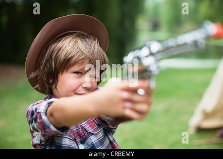 Boy in cowboy hat with toy pistol - Stock Photo