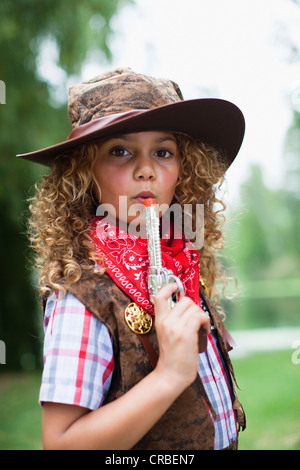 Girl in cowboy hat with toy pistol - Stock Photo