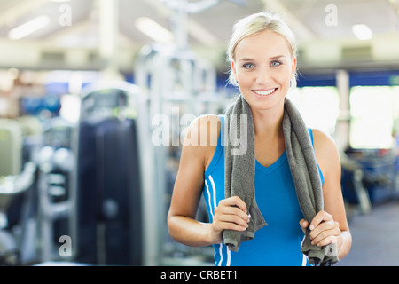 Woman holding towel around neck in gym - Stock Photo